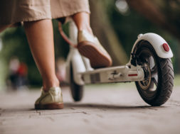 Young woman riding scooter in park feet close up